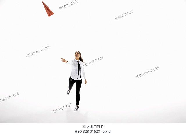 Businesswoman throwing paper airplane against white background