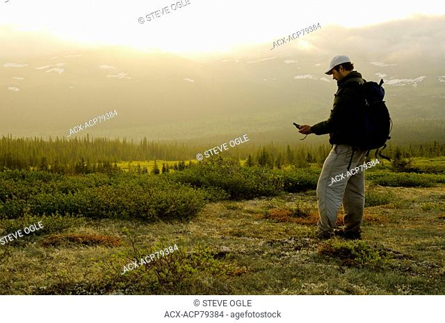 A hunter uses a GPS to find his location in the Caribou Range of northeastern British Columbia