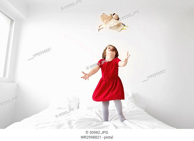 A young girl in a red dress jumping on a bed throwing her toy in the air