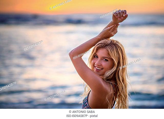 Portrait of young woman with arms raised on beach at sunset