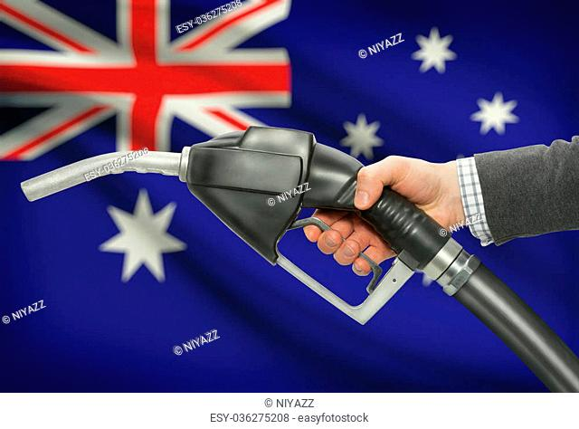 Fuel pump nozzle in hand with flag on background - Australia