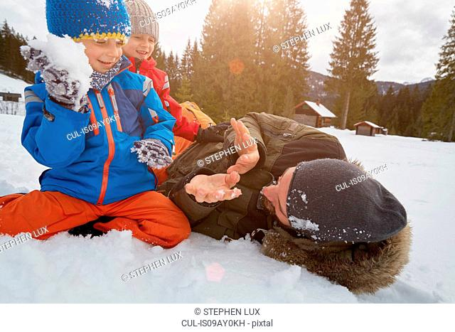 Father and sons having snowball fight in winter, Elmau, Bavaria, Germany