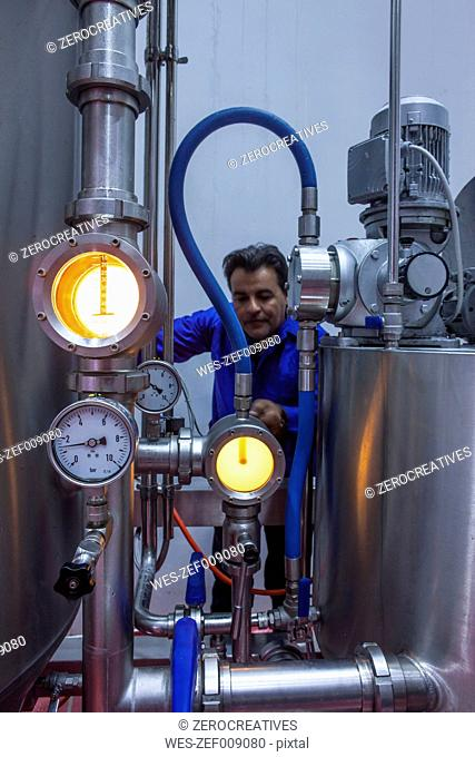 Worker in winery checking pressure gauge