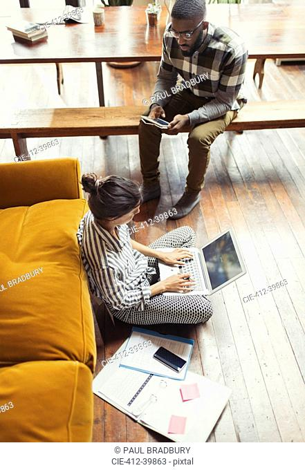 Female freelancer working at laptop on living room floor