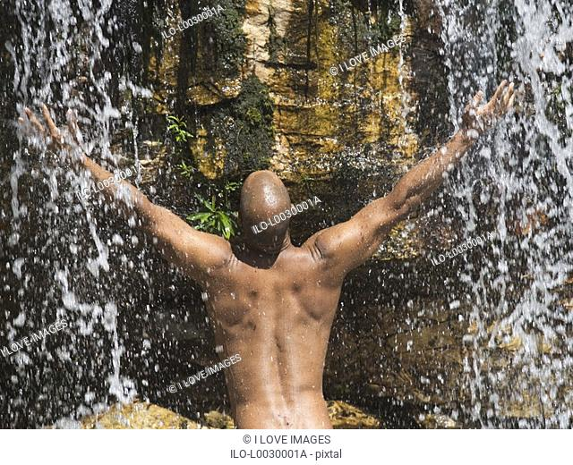 Young man standing in a waterfall