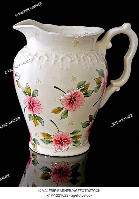 This stock image is a cream colored, floral water pitcher for home decor accent use, isolated on a black background with a beautiful reflected image in the...