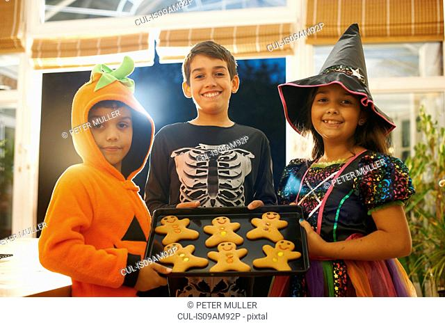 Brothers and sister wearing halloween costumes holding tray of gingerbread men