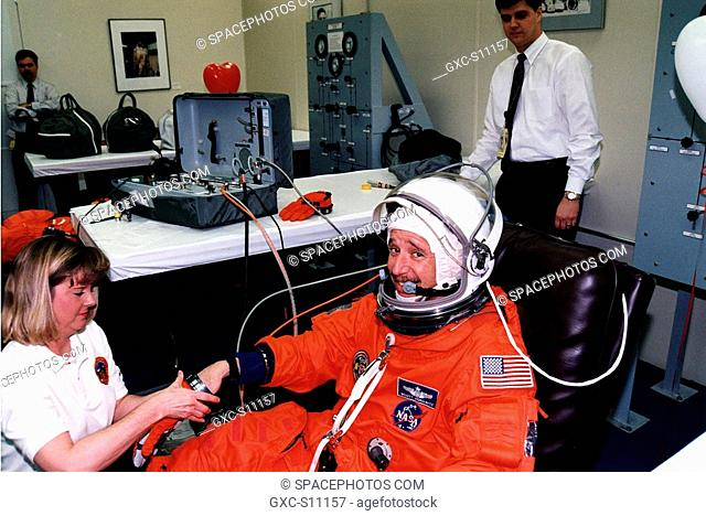02/11/1997 --- STS-82 Pilot Scott J. Doc Horowitz puts on a glove of his launch and entry suit with assistance from a suit technician in the Operations and...