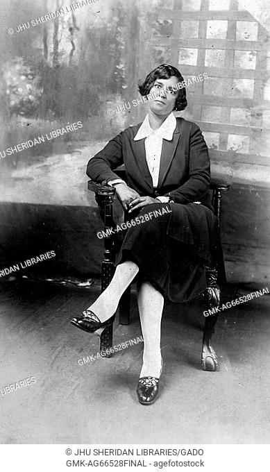 Full length sitting portrait, young African American woman, wearing dark dress with light blouse, sitting in front of backdrop, neutral expression, 1920