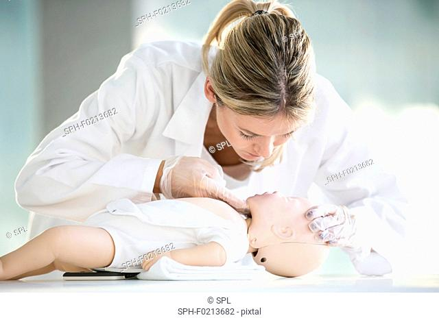 Doctor practising infant CPR
