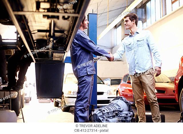 Mechanic and customer handshaking in auto repair shop
