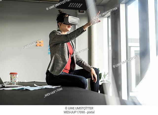 Businesswoman sitting on desk in office wearing VR glasses