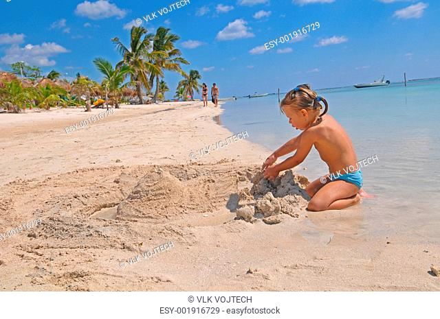 Picture of a little girl playing with the sand on the Mahahual beach
