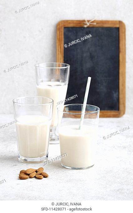 Three glasses of vegan almond milk and almonds