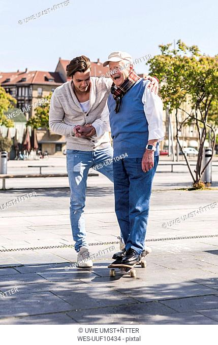Adult grandson assisting senior man on skateboard