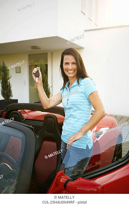 Girl proudly showing her key to a car