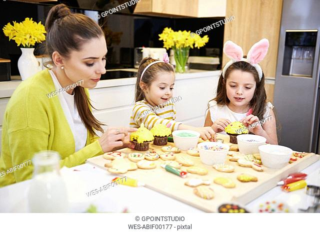Mother with daughters decorating Easter cookies and muffins in kitchen