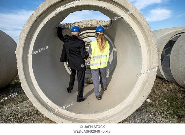 Businessman and female worker standing inside concrete pipe on industrial site