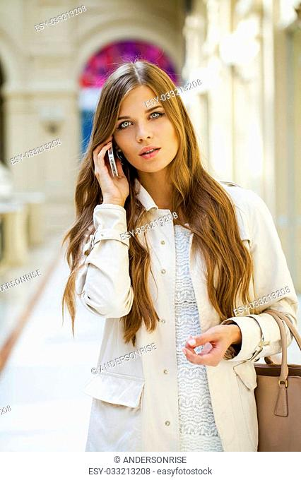 Beautiful young woman in white dress walks in the shop