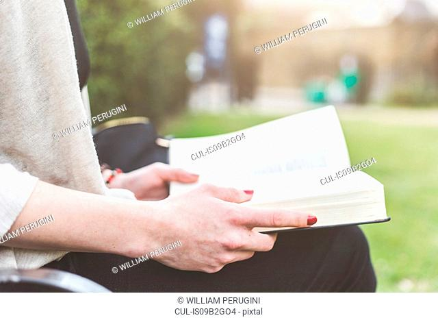 Cropped view of woman holding open book, London, UK