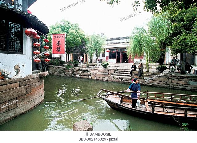 Woman rowing boat in canal, Jiaozhi Town, Kunshan City, Jiangsu Province of People's Republic of China