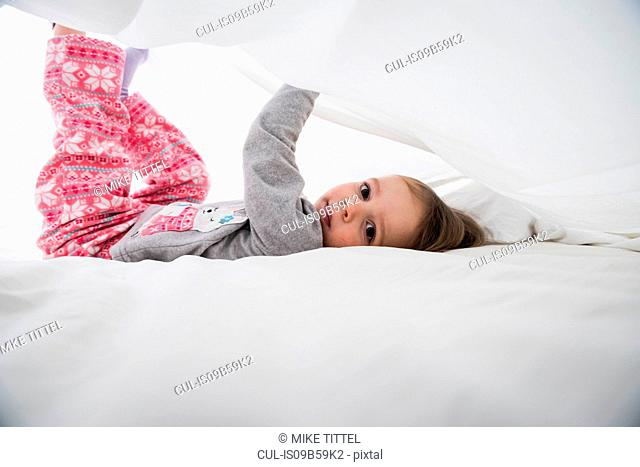 Portrait of female toddler lying between white bed sheets