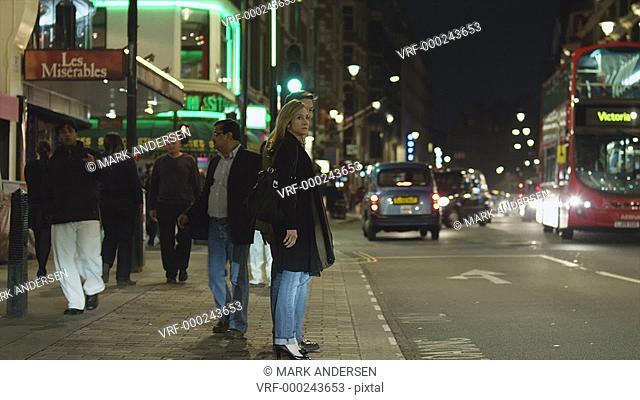 WS PAN Couple walking in downtown at night / Soho, London, UK