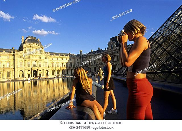 young tourist people, Louvre Pyramid by Ming Pei, in the main courtyard Cour Napoleon of Palais du Louvre, 1st arrondissement, Paris, Ile de France region