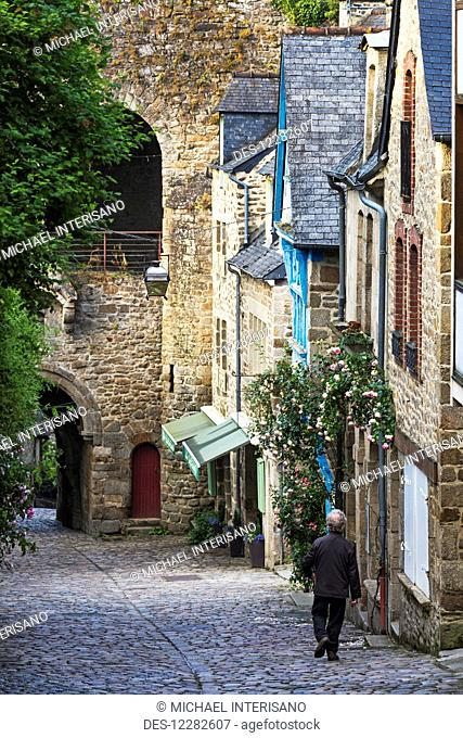 Male walking down a cobblestone road framed with old stone buildings and stone wall in the distance; Dinan, Brittany, France