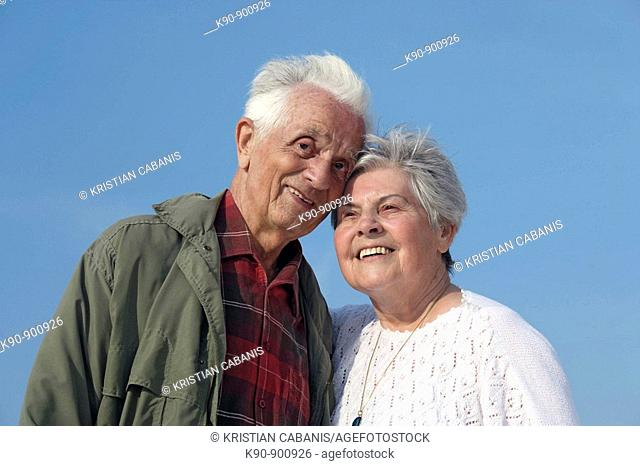 Half body image of elderly caucasian couple smiling and looking into the camera with bright blue sky in the background, Island of Amrum, Northfrisian