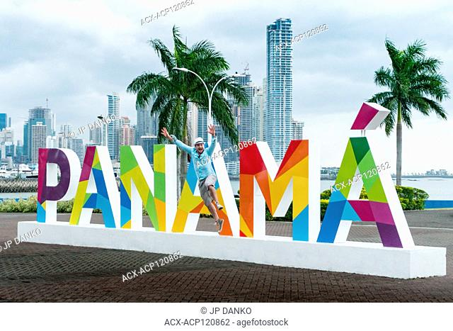 Man jumps from a Colourful Panama sign in Panama City, Central America