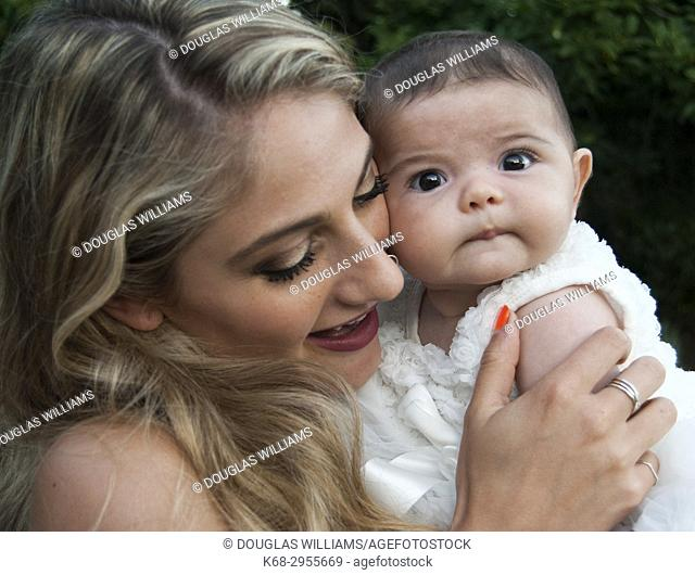 A young woman, 21, with a baby, 3 months old, at an outdoor wedding in West Vancouver, BC, Canada