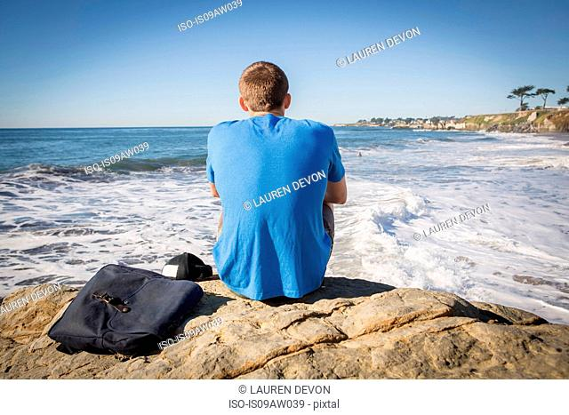 Young man sitting by rock, looking out to sea, rear view