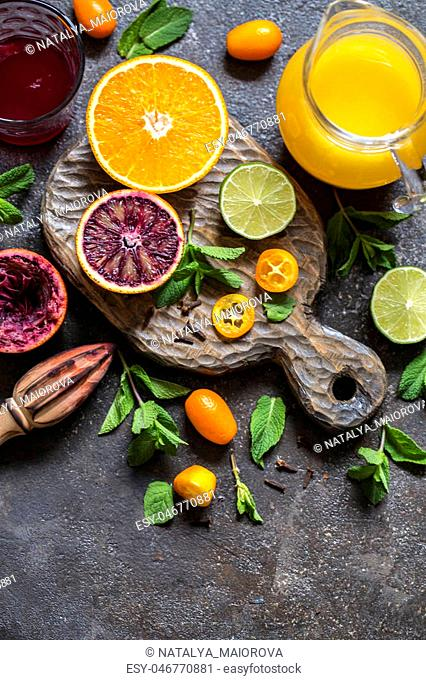 set of citrus fruits orange red, lemon, kumquat and citrus juice on wooden Board