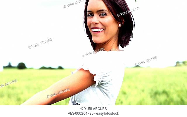Cute young woman smiling and laughing while holding some wheat and twirling around