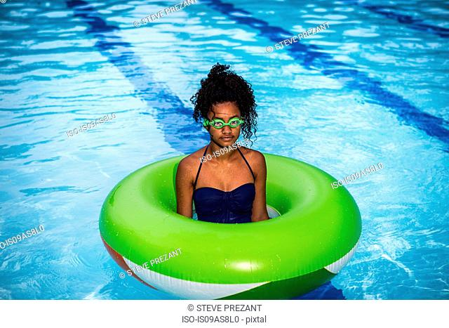 Girl standing in inflatable ring in swimming pool, wearing goggles looking at camera