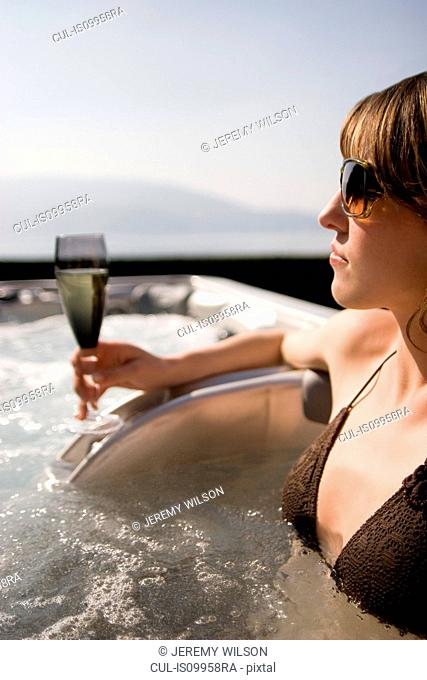 Young woman in spa with glass of champagne