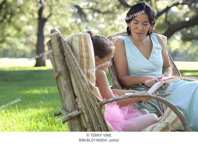 Elegant mother and daughter reading books in backyard