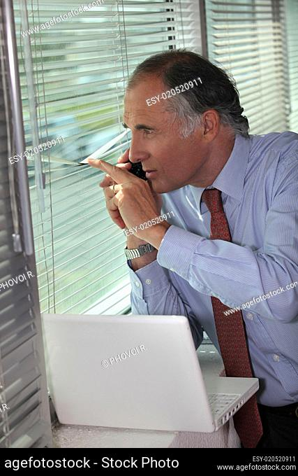 A businessman looking through the blinds