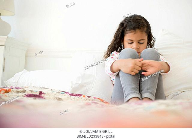 Unhappy Mixed Race girl sitting on bed