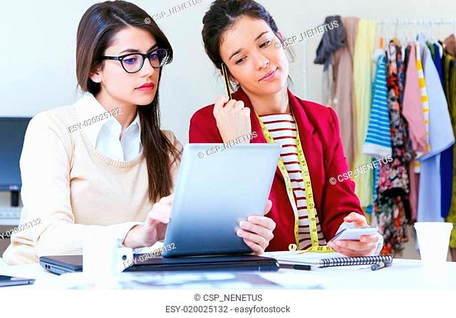 Two young businesswomen working with digital tablet in her office