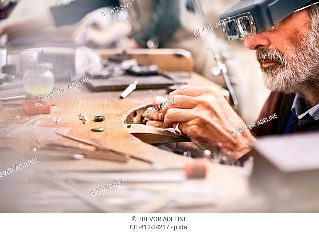 Male jeweler using headband magnifier making jewelry in workshop