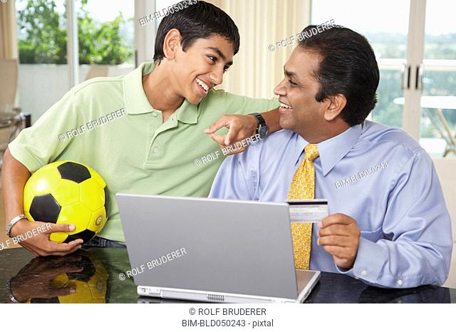 Middle Eastern father and son shopping online