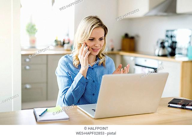 Woman with laptop and cell phone working at home