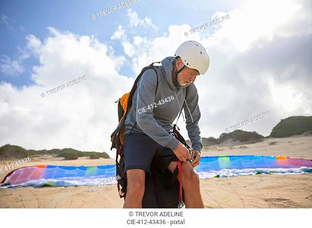 Male paraglider preparing on sunny beach