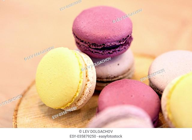 cooking, confectionery and baking concept - close up of different macarons on wooden stand