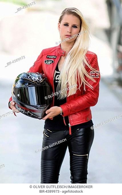 Young woman with long blonde long hair poses posing with motorcycle helmet