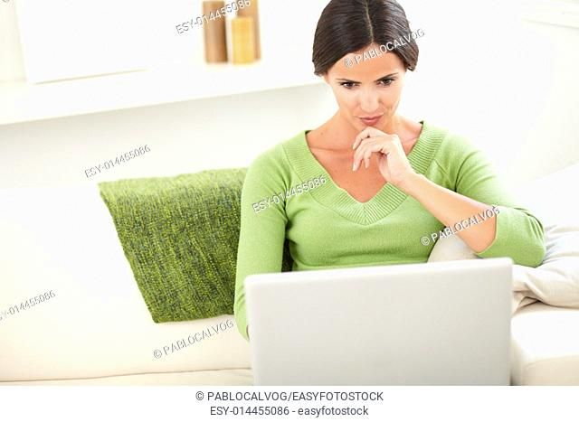 Waist up portrait of a concentrated person using a laptop while sitting inside the house