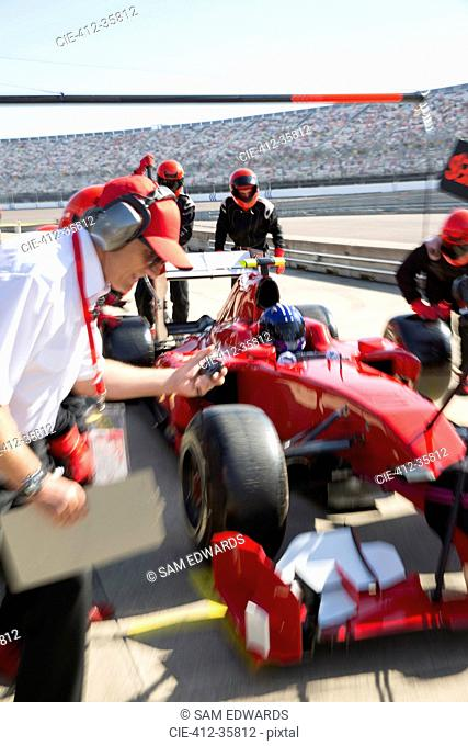 Manager with stopwatch timing pit crew replacing tires on formula one race car in practice session pit lane