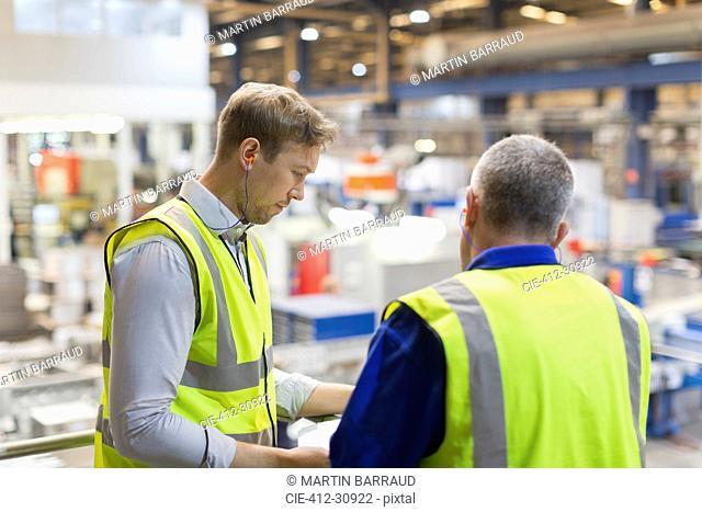 Supervisors talking on platform above steel factory